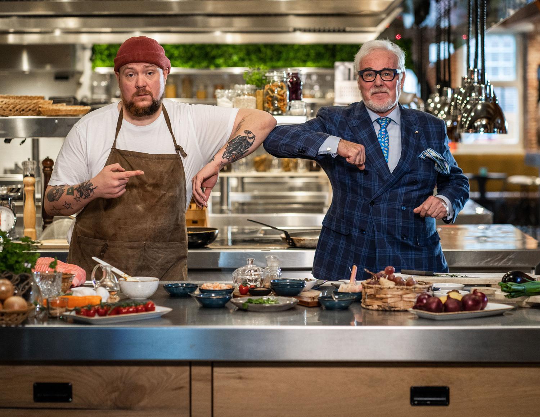 Foto van Nick Toet en Alain Caron die in een keuken staan met ieder een belegd bord in hun hand